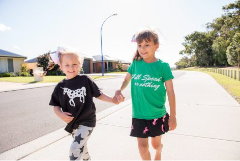kids in Kingston Estate holding hands near new houses and new facilities